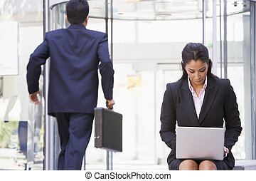 Businesswoman working at laptop outside