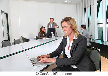 Businesswoman working in office with laptop computer