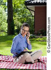 Businesswoman working in the garden