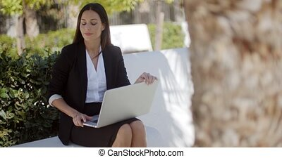 Businesswoman working on a laptop in a park