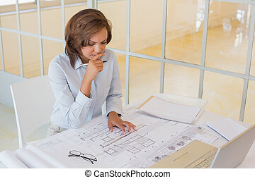 Businesswoman working on blueprints in office