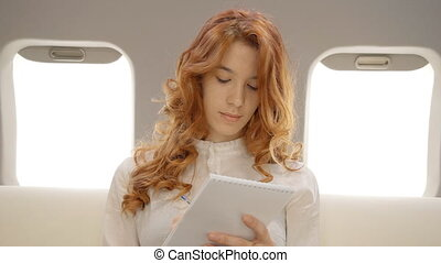 Businesswoman working on business plan in private aircraft....