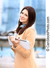 Businesswoman working on digital tablet out of office overlooking cityscape