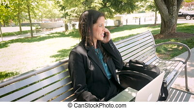 Businesswoman working on her laptop and talking on her...