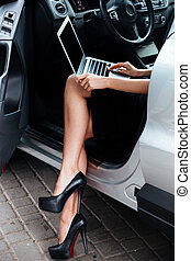 Businesswoman working on her laptop computer while sitting in car