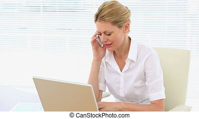 Businesswoman working on laptop and phone