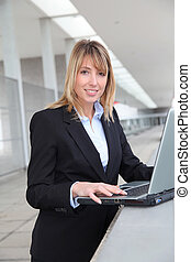 Businesswoman working on laptop computer outside