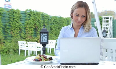 Businesswoman working on laptop in cafe