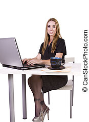 Businesswoman  working on laptop with cup of coffee on her desk