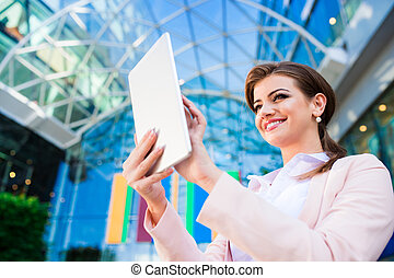 Businesswoman working on tablet against glassy modern office building