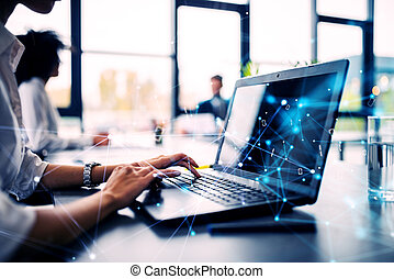 Businesswoman works in office with a laptop with internet network effects. Concept of internet sharing and company startup