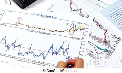 Businesswoman works with graphics on paper and tablet. Stock market