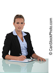 businesswoman writing at her desk