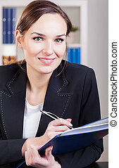 Businesswoman writing in a notebook
