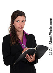 Businesswoman writing in a pad