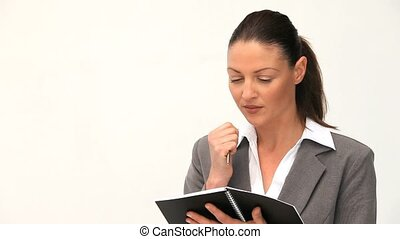 Businesswoman writing in her agenda