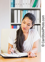 Businesswoman writing notes in diary