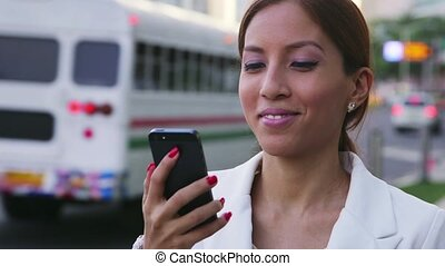 Hispanic businesswoman using mobile phone in city street