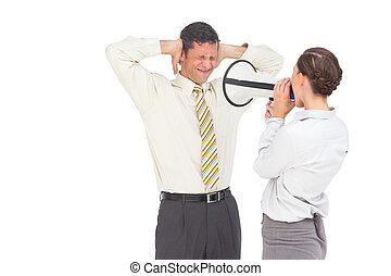 Businesswoman yelling at businessman with megaphone