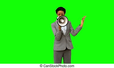 Businesswoman yelling into a megaphone on green screen in...