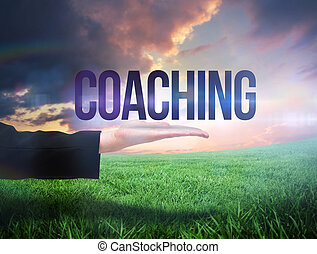 Businesswomans hand presenting the word coaching