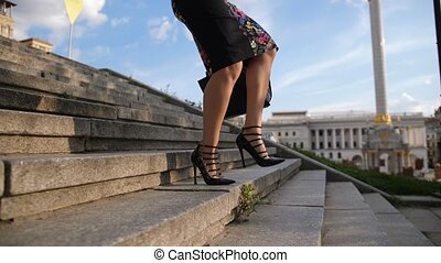 Businesswoman's legs in heels stepping down stairs -...