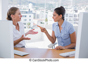 Businesswomen arguing at their desk in the office