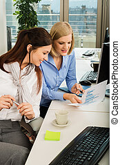 Businesswomen Discussing Graph In Office