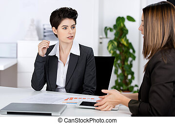 Businesswomen Discussing In Meeting At Desk
