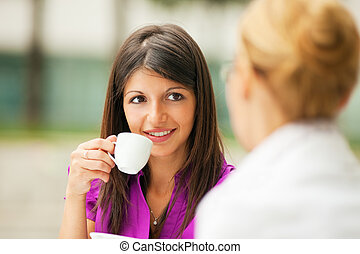 businesswomen drinking coffee - two business women drinking...