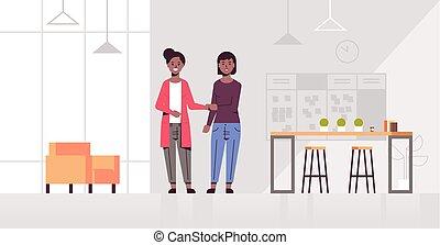 businesswomen handshaking african american business partners hand shake during meeting agreement partnership concept creative co-working center modern office interior full length horizontal