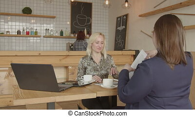 Businesswomen handshaking making deal in cafe