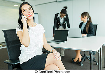 Businesswomen in an office working on a laptop and calling potential partners