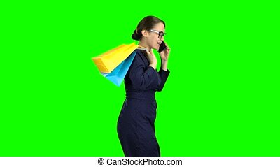 Businesswomen in glasses speaks on the phone and goes to the...