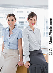 Businesswomen leaning on desk