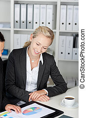 Businesswomen Looking At Pie Chart At Desk