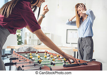 businesswomen playing table football