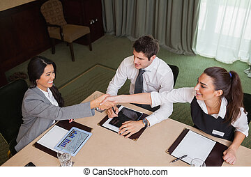 Businesswomen reaching agreement in conference room