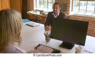Businesswomen reviewing job resume and hires latino man for...