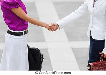 businesswomen shaking hands - cropped view of two business ...