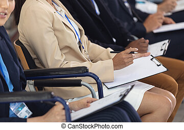 Businesswomen sitting while listening to speech in conference room