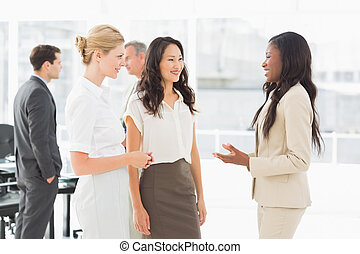 Businesswomen speaking together in conference room in the office