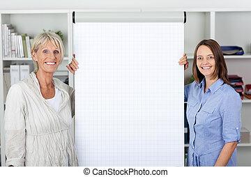 Businesswomen Standing By Flipchart In Office