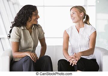 Businesswomen talking in lobby - Businesswomen talking in ...