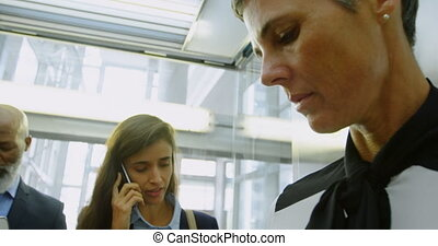 Businesswomen traveling in elevator in office 4k - Close-up...