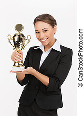 Businesswomen with business trophy. Beautiful young businesswomen holding her business trophy while standing isolated on white