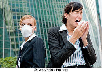 Businesswomen With Cold - A businesswoman sneezing as...