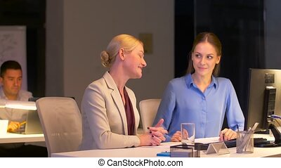 businesswomen with computer working late at office