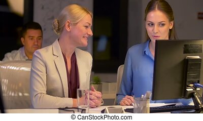 businesswomen with computer working late at office -...