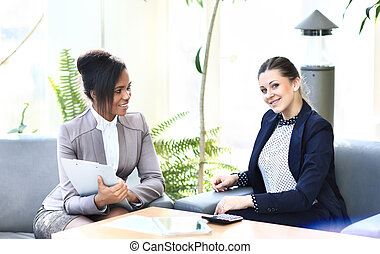 Businesswomen With Digital Tablet Sitting In Modern Office and discuss business matters